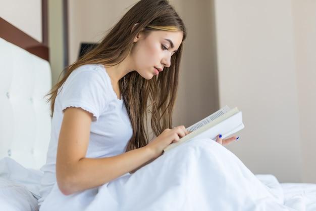 Szczęśliwa młoda kobieta relaksuje się w domu i czyta książkę