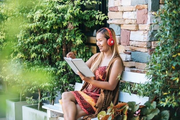 Szczęśliwa młoda kobieta relaksuje z słucha ulubioną muzykę przy kawiarnią