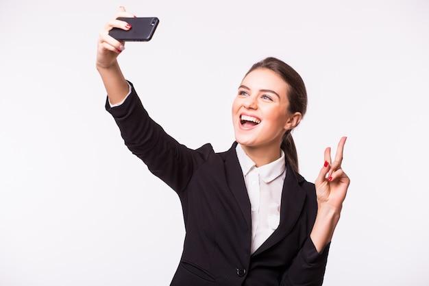 Szczęśliwa młoda kobieta robi selfie zdjęcie na smartfonie na białej ścianie