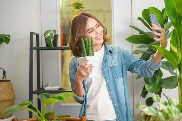 Szczęśliwa młoda kobieta robi selfie ze swoimi roślinami i prowadzi wideorozmowę w domu
