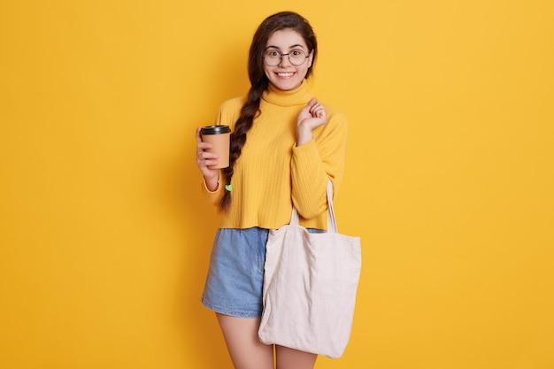 Szczęśliwa młoda kobieta robi zakupy i cieszy się gorącego napój