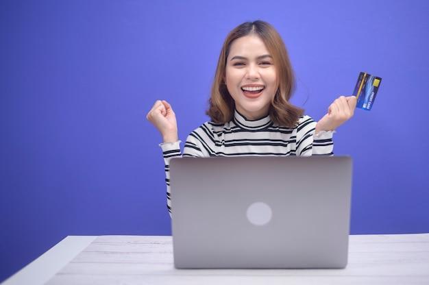 Szczęśliwa młoda kobieta robi zakupy online przez laptop, trzymając kartę kredytową