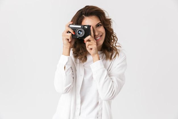 Szczęśliwa młoda kobieta robienie zdjęć aparatem fotograficznym na białym tle