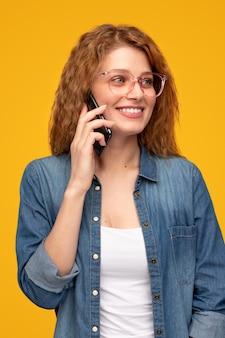 Szczęśliwa młoda kobieta rozmawia na smartfonie