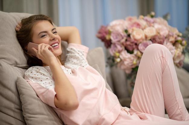 Szczęśliwa młoda kobieta rozmawia przez inteligentny telefon w domu. atrakcyjna kobieta dzwoniąc przez telefon w pomieszczeniu.