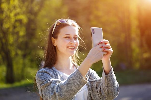 Szczęśliwa młoda kobieta rozmawia przez połączenie online w smartfonie. na zewnątrz w słoneczny wiosenny dzień w parku