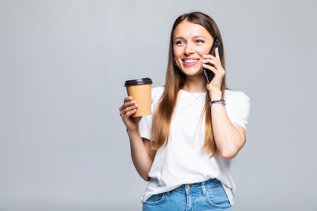 Szczęśliwa młoda kobieta rozmawia przez telefon komórkowy mając kawę