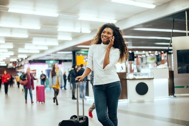 Szczęśliwa młoda kobieta rozmawia przez telefon na lotnisku.