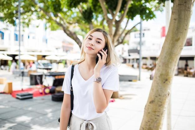 Szczęśliwa młoda kobieta rozmawia telefon na portret ulicy stylu życia miasta w okresie letnim