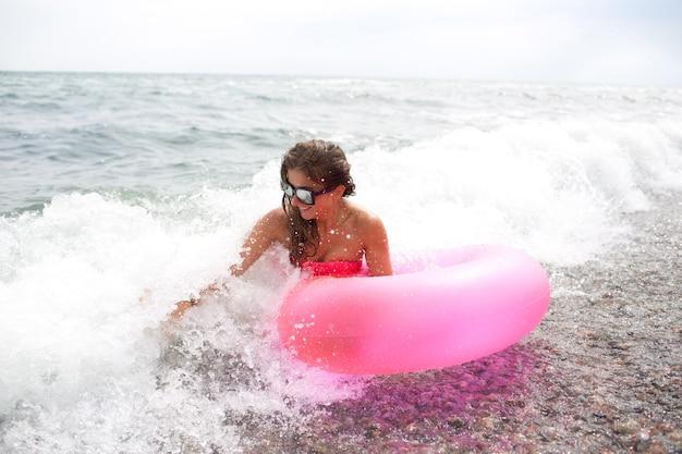 Szczęśliwa młoda kobieta siedzi na brzegu morza lub oceanu w falach z różowym materacem w ręku i ciesz się.