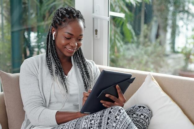 Szczęśliwa młoda kobieta siedzi na kanapie w domu i używa aplikacji na tablecie do komunikacji z przyjaciółmi, członkami rodziny i współpracownikami