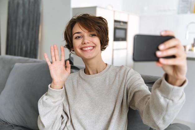 Szczęśliwa młoda kobieta siedzi na kanapie w domu, przy użyciu telefonu komórkowego, nawiązywanie połączenia wideo