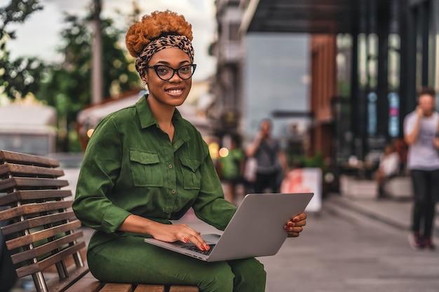 Szczęśliwa młoda kobieta siedzi na ławce i pracuje z laptopem podczas pisania