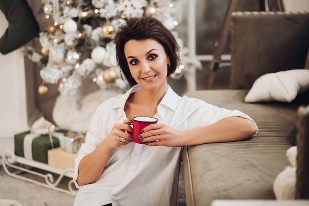 Szczęśliwa młoda kobieta siedzi na podłodze, jednocześnie ciesząc się gorącym napojem