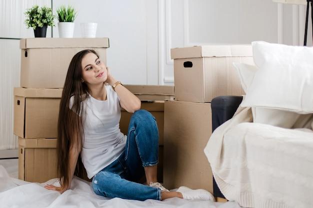 Szczęśliwa młoda kobieta siedzi na podłodze w swoim nowym mieszkaniu