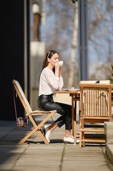 Szczęśliwa młoda kobieta siedzi na tarasie kawiarni w słoneczny dzień i pije kawę. kobieta korzystających z pierwszego wiosennego słońca na świeżym powietrzu.