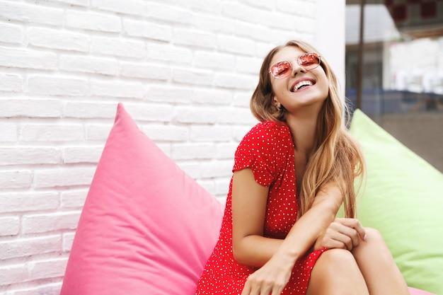 Szczęśliwa młoda kobieta siedzi na zewnątrz na krześle worek fasoli i śmieje się z radości