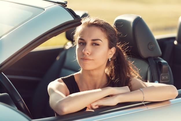 Szczęśliwa młoda kobieta siedzi w swoim samochodzie