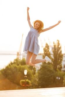 Szczęśliwa młoda kobieta skacze outdoors w sukni