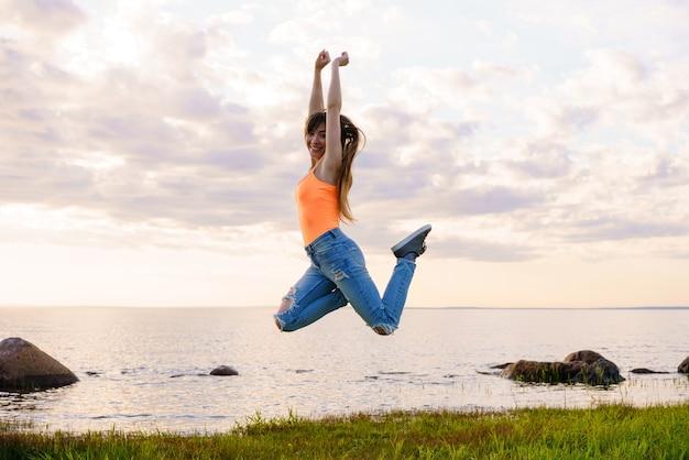 Szczęśliwa młoda kobieta skoki na przestrzeni rzeki o zachodzie słońca