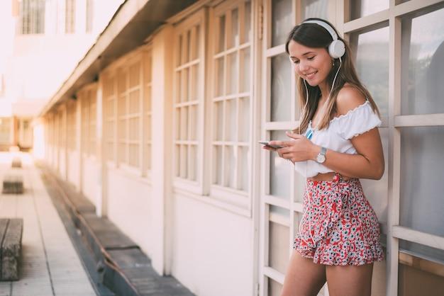 Szczęśliwa młoda kobieta słucha muzyka na telefonie komórkowym