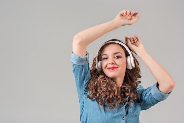 Szczęśliwa młoda kobieta słucha muzyki przez słuchawki