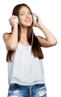 Szczęśliwa młoda kobieta słuchania muzyki w słuchawkach