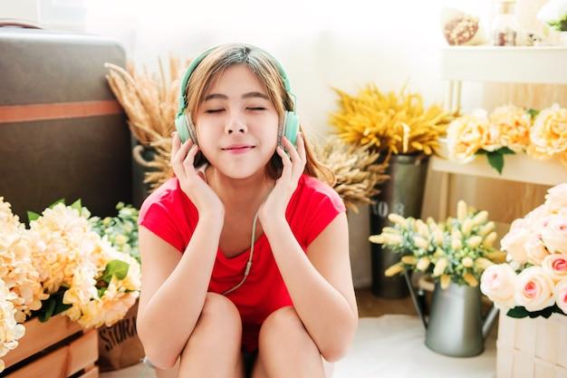 Szczęśliwa młoda kobieta słuchania muzyki z inteligentnego telefonu w przytulnym domu