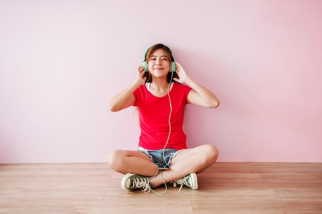 Szczęśliwa młoda kobieta słuchania muzyki z telefonu komórkowego w domu