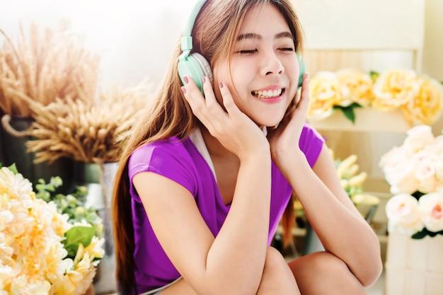Szczęśliwa młoda kobieta słuchania muzyki za pośrednictwem inteligentnego telefonu
