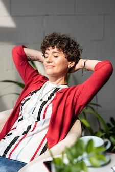 Szczęśliwa młoda kobieta spokojny, trzymając ręce za głową, siedząc przed oknem i ciesząc się słoneczny dzień