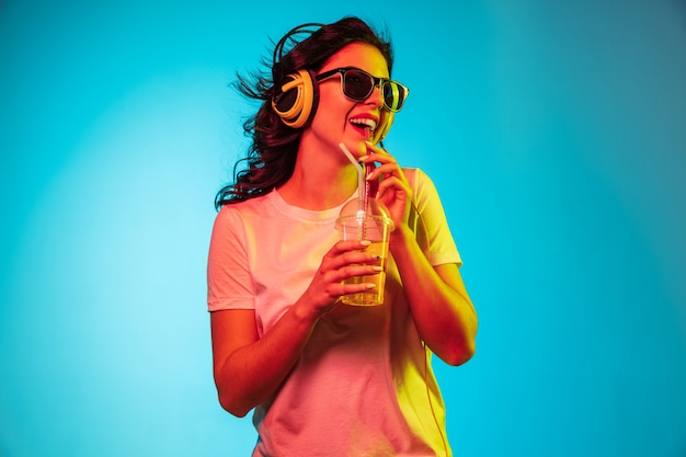 Szczęśliwa młoda kobieta, stojąc i uśmiechając się przed niebieskim