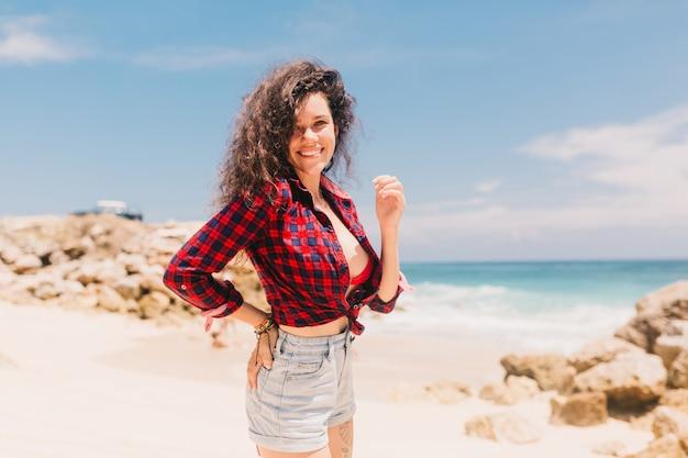 Szczęśliwa młoda kobieta stojąc na plaży