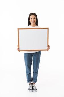 Szczęśliwa młoda kobieta stojąca na białym tle nad białą ścianą, trzymająca pustą tablicę