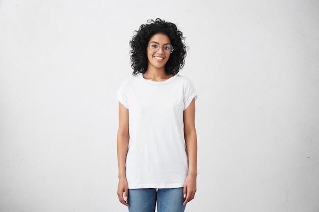 Szczęśliwa młoda kobieta stojąca przy pustej białej ścianie