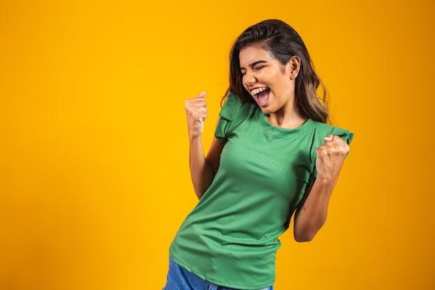 Szczęśliwa młoda kobieta świętuje z koncepcją osiągnięcia. tak