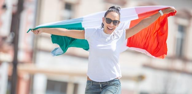 Szczęśliwa młoda kobieta świętuje zwycięstwo włoch na ulicy trzymając flagę i skacząc z radości.