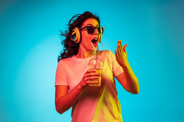 Szczęśliwa młoda kobieta tańczy i uśmiecha się w słuchawkach nad modnym niebieskim neonowym studiem