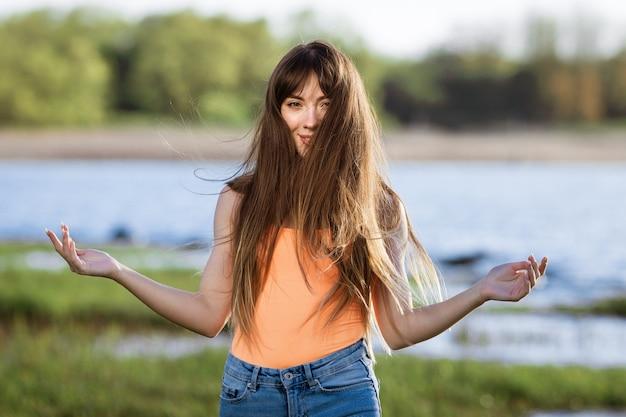 Szczęśliwa młoda kobieta tańczy w słuchawkach na brzegu zatoki słońce słoneczny wiosenny dzień