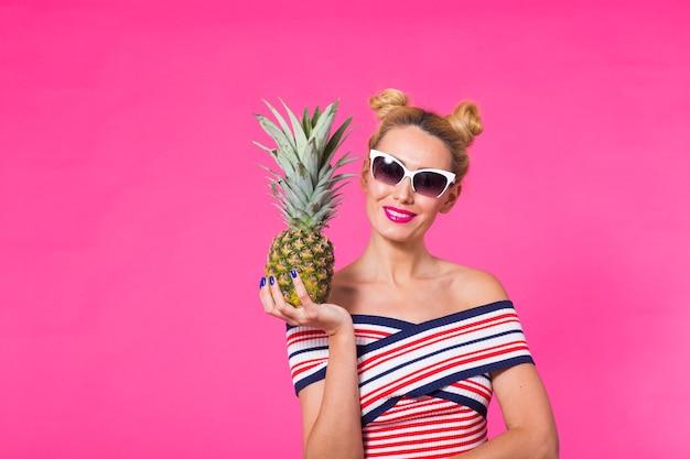 Szczęśliwa młoda kobieta trzyma ananas na różowym tle z copyspace. koncepcja lato, dieta i wakacje
