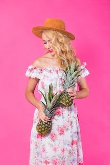 Szczęśliwa młoda kobieta trzyma ananasa na różowej ścianie