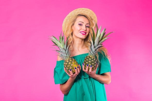 Szczęśliwa młoda kobieta trzyma ananasa na różowym tle. koncepcja lato, dieta i wakacje