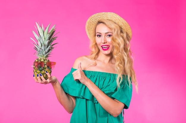 Szczęśliwa młoda kobieta trzyma ananasa