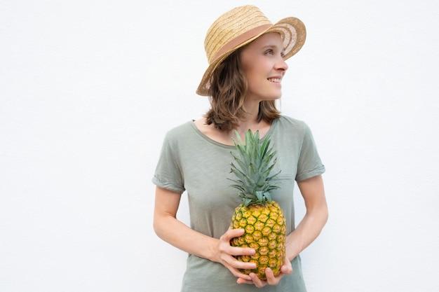 Szczęśliwa młoda kobieta trzyma cały ananasa w słomianym kapeluszu