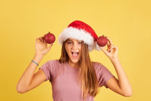 Szczęśliwa młoda kobieta trzyma czerwone bombki i nosi kapelusz świętego mikołaja na żółtym tle