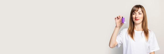 Szczęśliwa młoda kobieta trzyma inhalator w dłoni, patrzy na inhalator. transparent. koncepcja ułatwiająca oddychanie, leczenie astmy, gardła, krtani, tchawicy