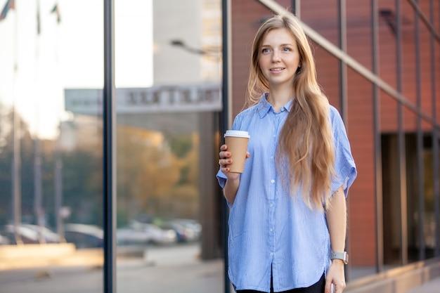 Szczęśliwa młoda kobieta trzyma kawę w jednorazowej filiżance, chodzi wzdłuż budynku