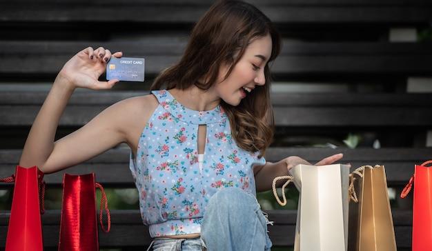 Szczęśliwa młoda kobieta trzyma kredytową kartę z torba na zakupy, wydaje pieniądze z cieszyć się robić zakupy.