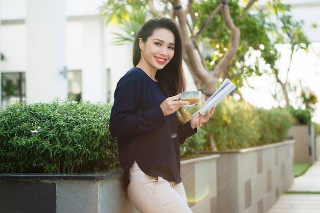 Szczęśliwa młoda kobieta trzyma książkę lubiącą literaturę analizującą powieść w czasie wolnym na tarasie kawiarni w kampusie w słoneczny dzień.