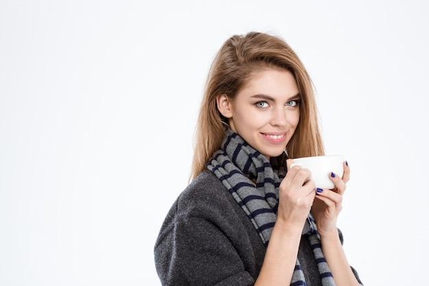 Szczęśliwa młoda kobieta trzyma kubek z kawą na białym tle